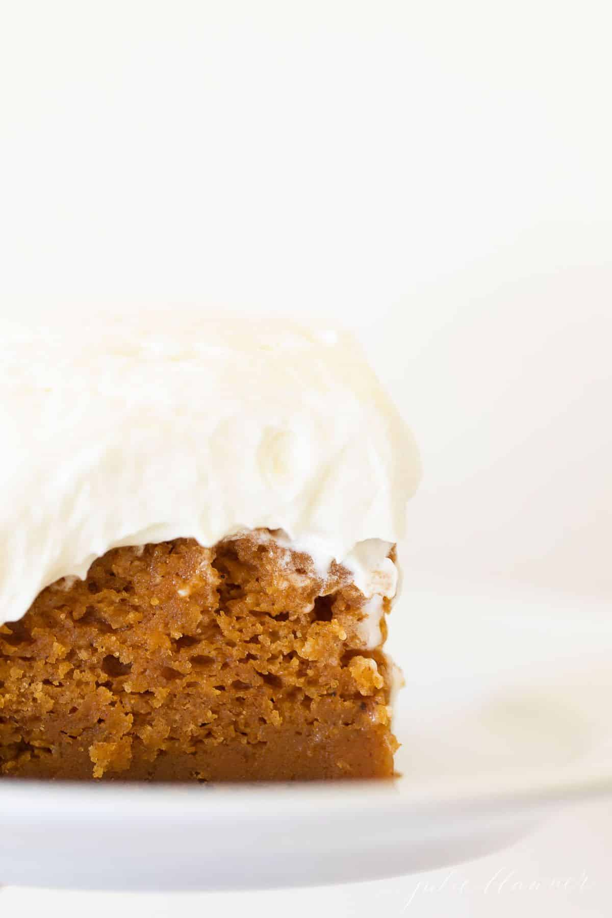 A piece of cake, frosted with fluffy cream cheese frosting on a white background.