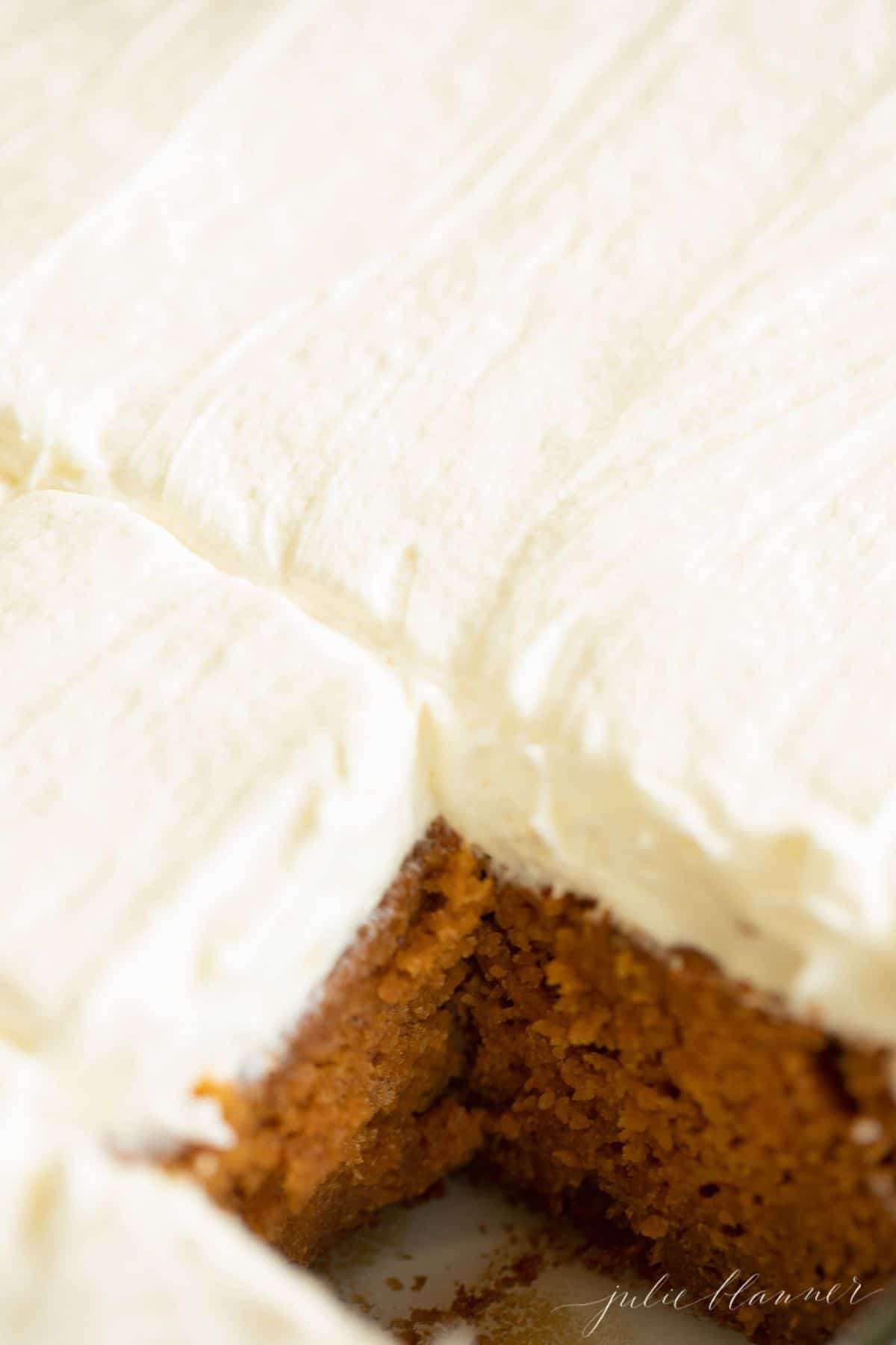 Close-up of sheet cake covered in frosting, one slice removed. #creamcheesefrostingrecipe