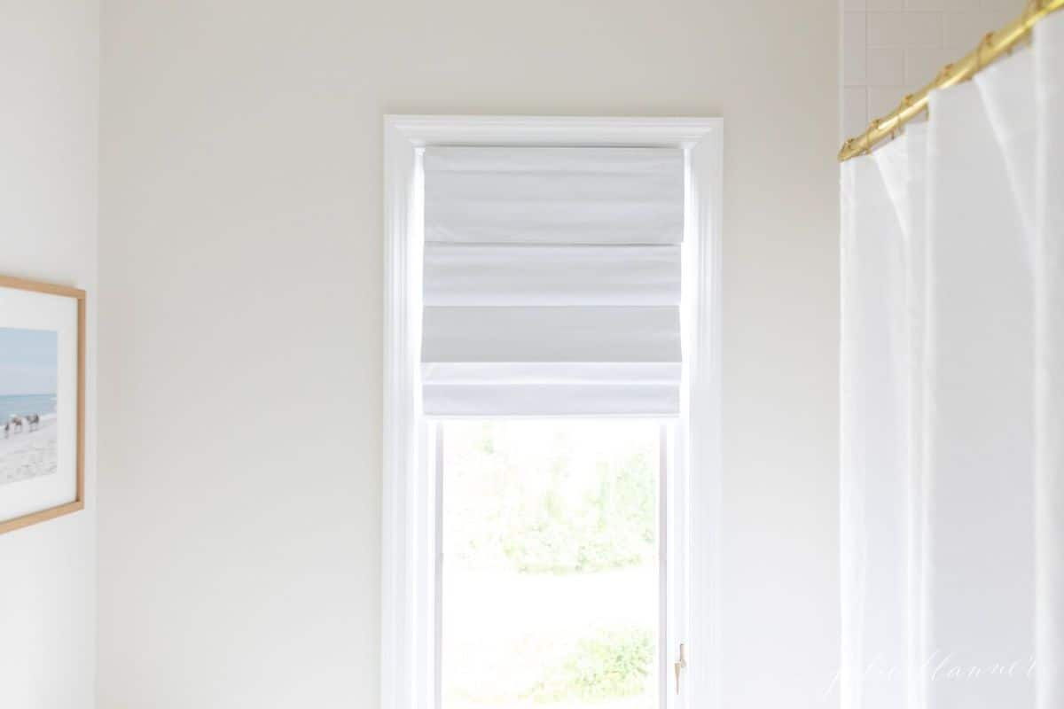 A white cordless shade in a vertical bathroom window.