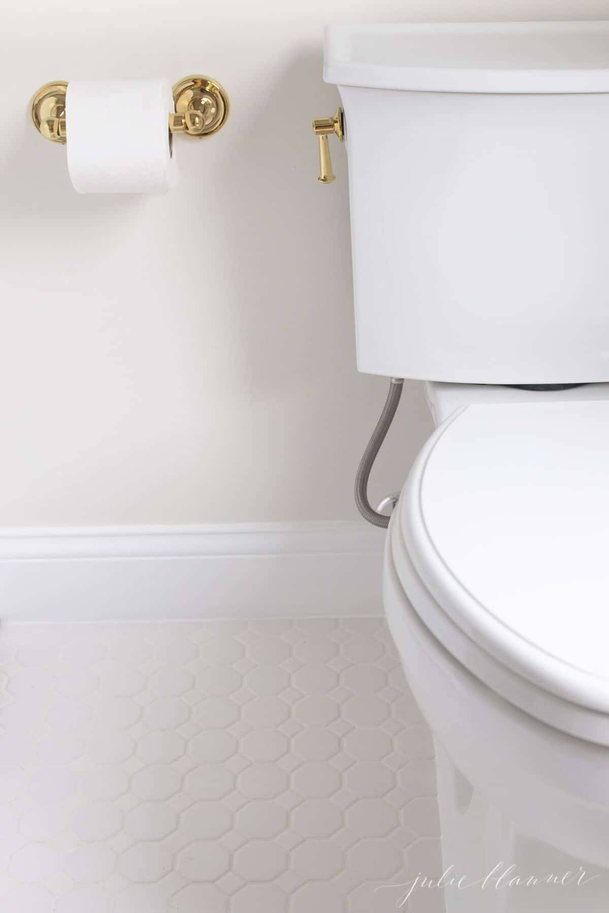 Close-up shot of white toilet, brass toilet paper holder and white mosaic tile floor.
