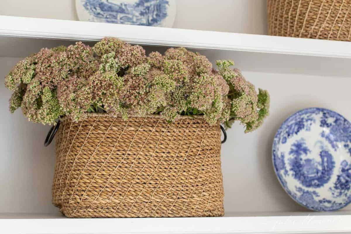 Large basket place on bookshelf, filled with fresh flowers. #falldecor