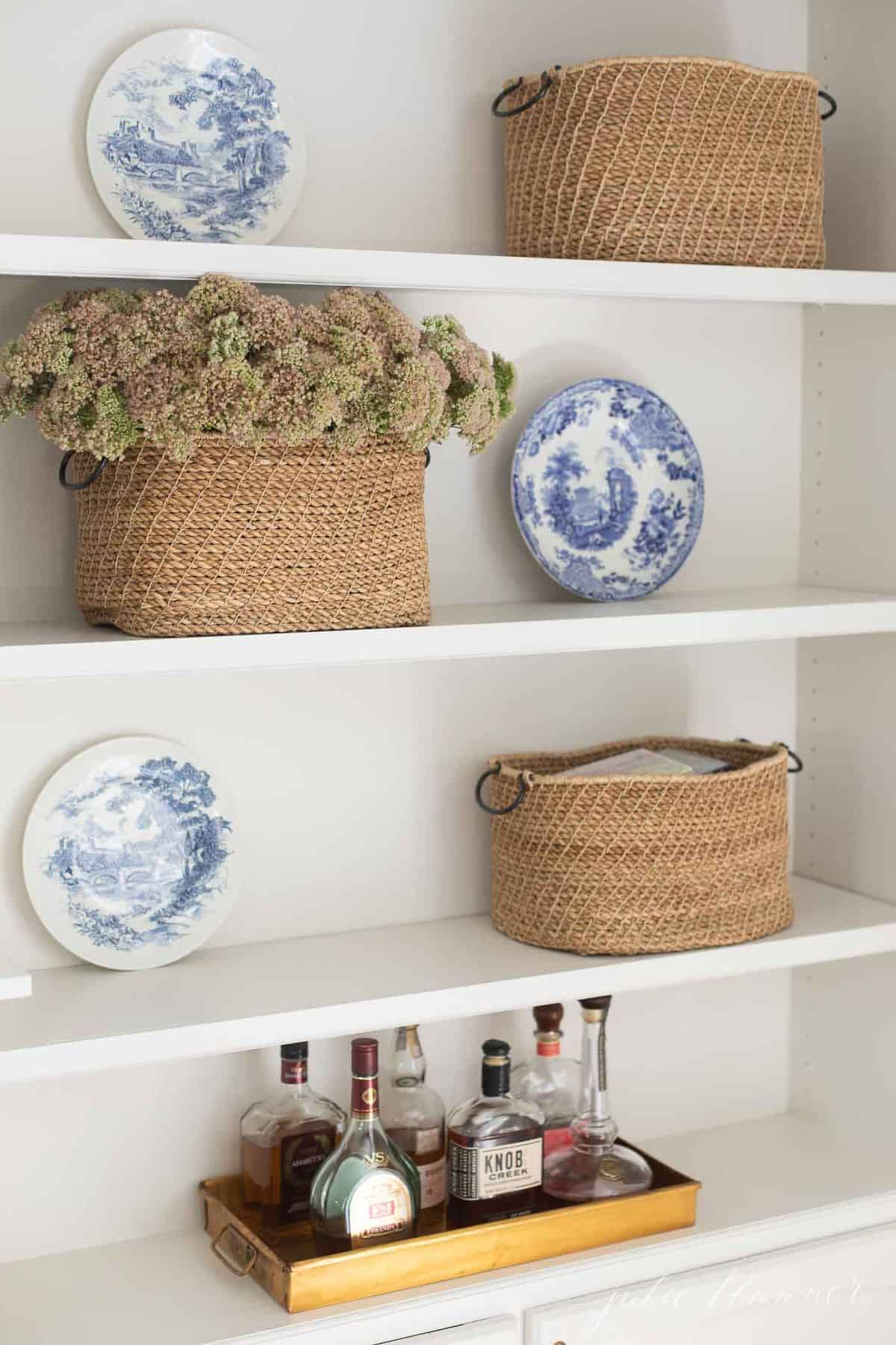 Built in book shelves with a tray of liquor, basket of flowers and blue and white plates. #falllivingroom