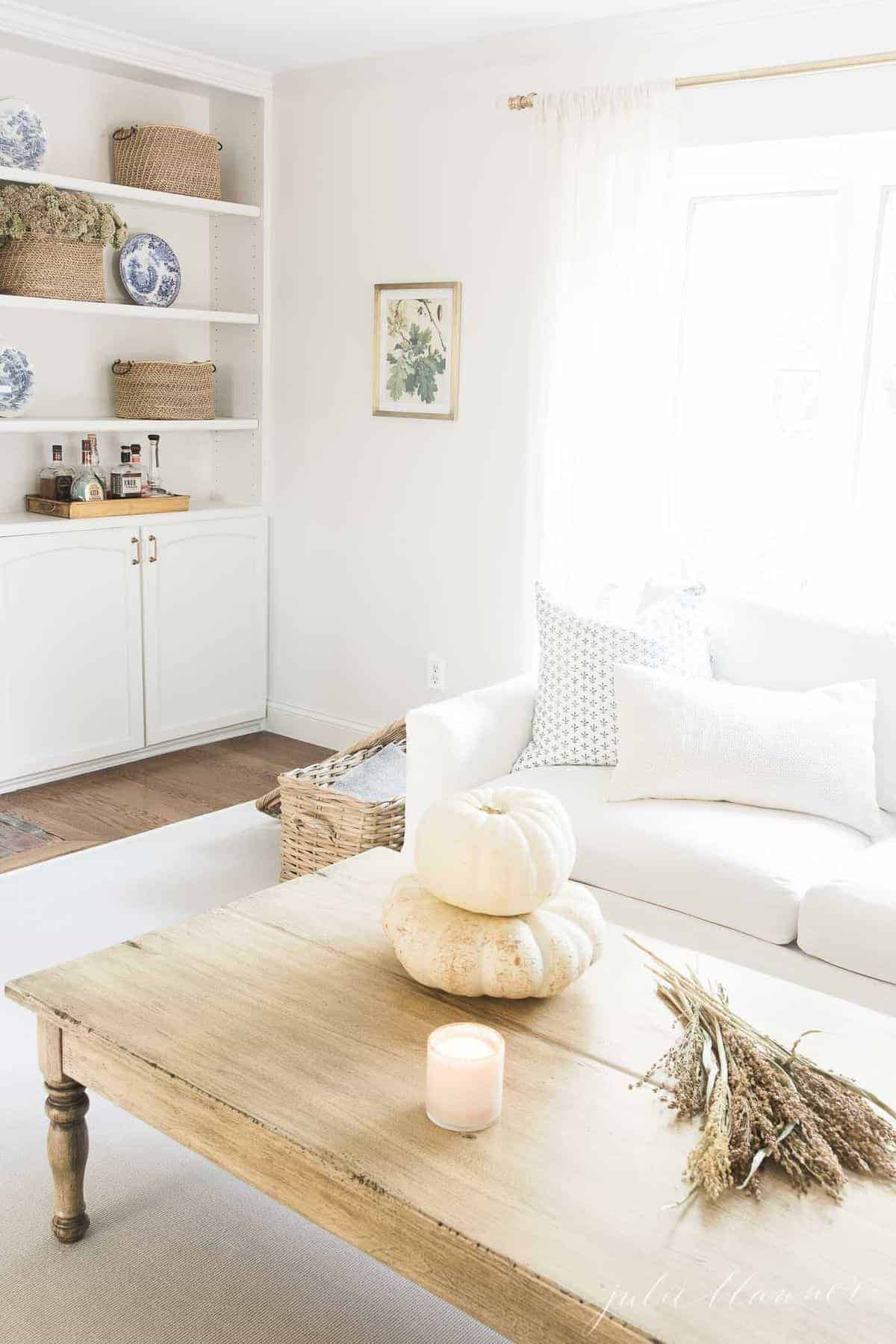 Living room featuring a white sofa, build in bookshelves, and fall decor such as a candle, fall foliage and white pumpkins on coffee table in foreground. #fallliviingroom #harvestdecor