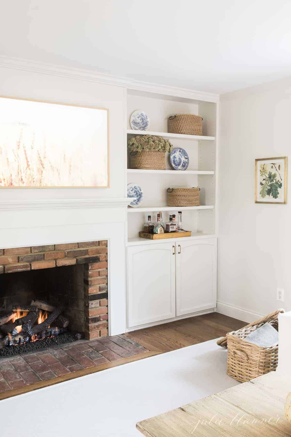 Living room fireplace burning with artwork above and bookshelves on the side. #falllivingroom