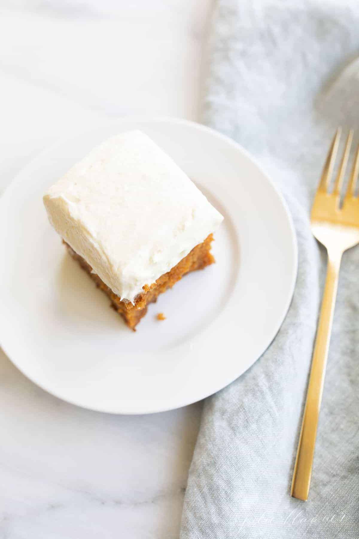 White counter with a white plate, slice of cake with cream cheese frosting and blue linen napkin, gold fork to the side. #creamcheesefrosting
