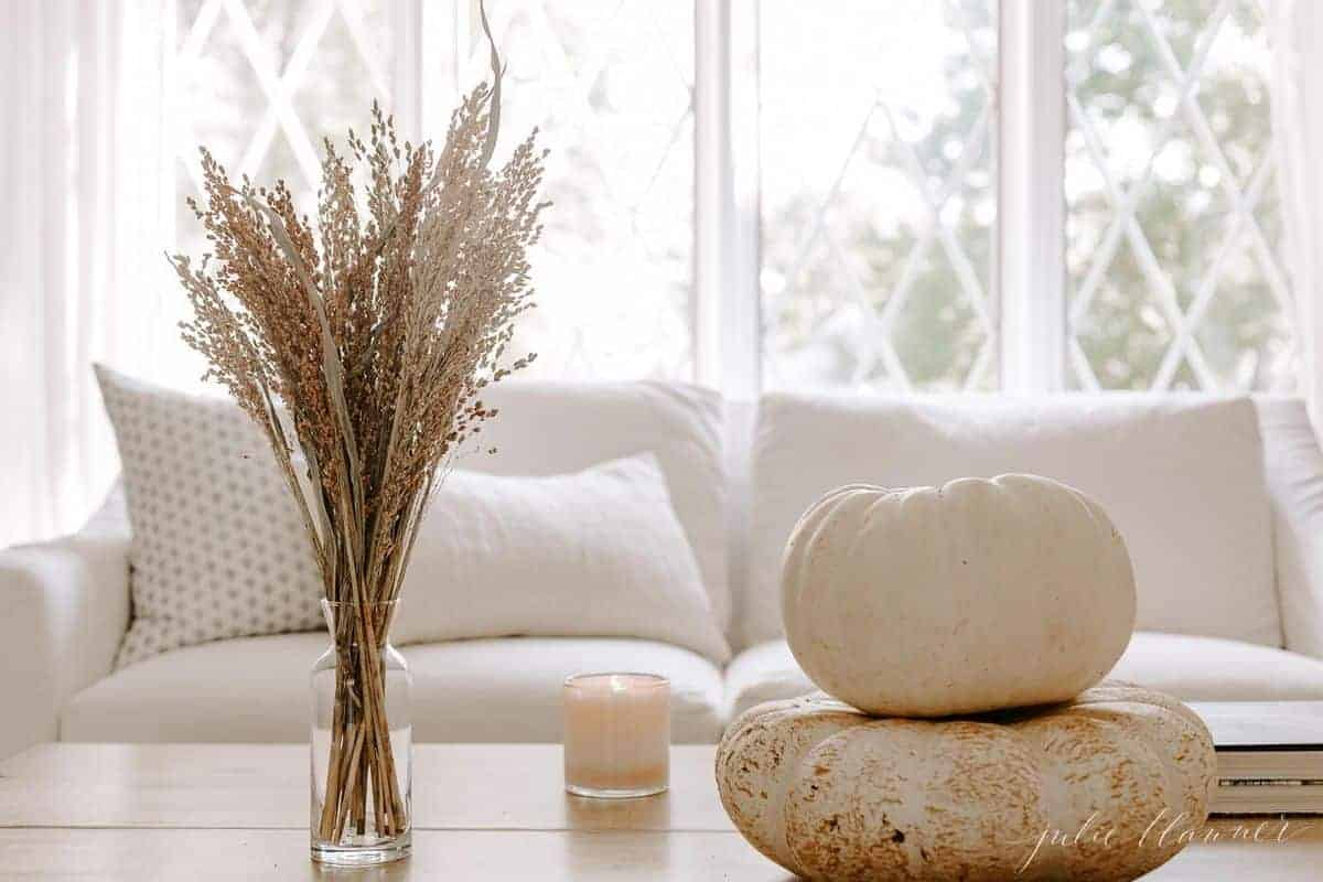 Wooden coffee table with white sofa and window in background, white pumpkins, candle and vase of fall foliage as decor. #falllivingroom #harvestdecor