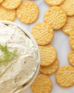 A white bowl of Boursin cheese spread on a marble counter top with crackers spread around. #homemadeboursin #boursincheeserecipe