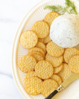 Boursin cheese ball on a cream platter with crackers and a cheese spreader. #boursincheese