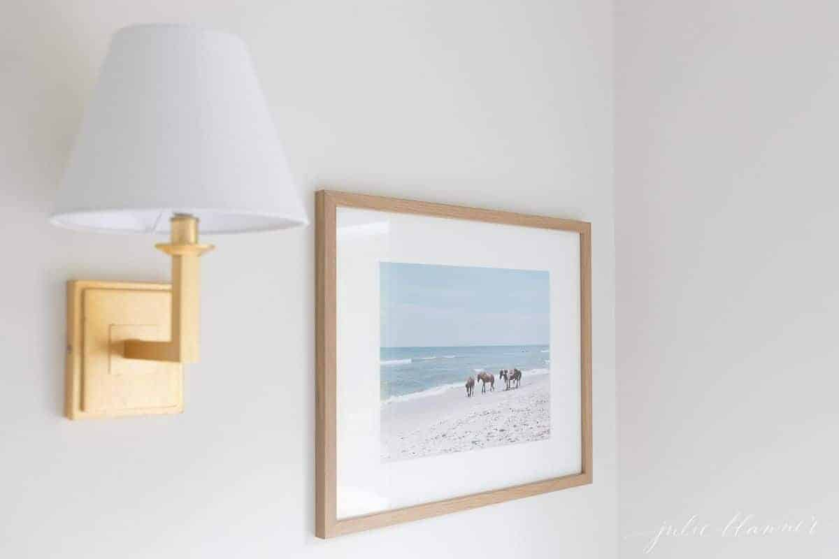 Edge of a gold sconce, and a raw wood framed photo of horses on a beach.