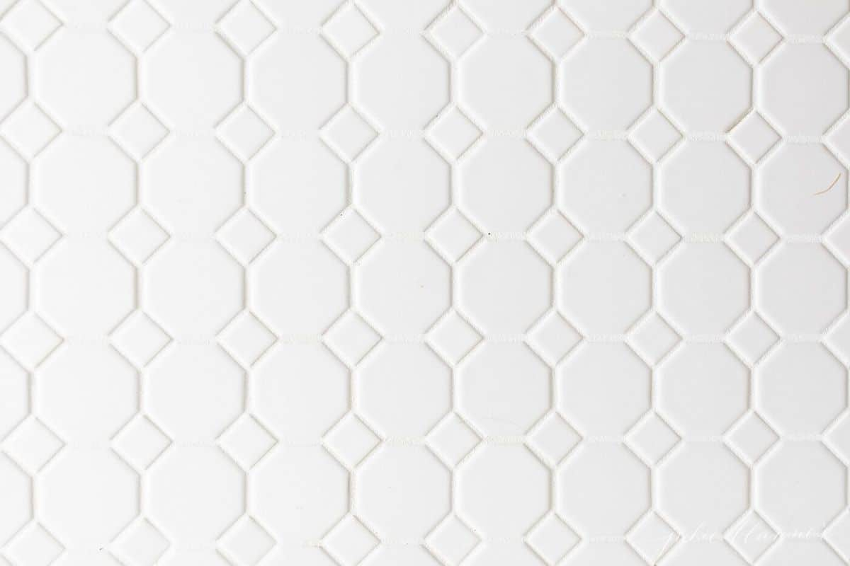 close-up shot of white honeycomb floor tile and white grout. #spabath #classicbath