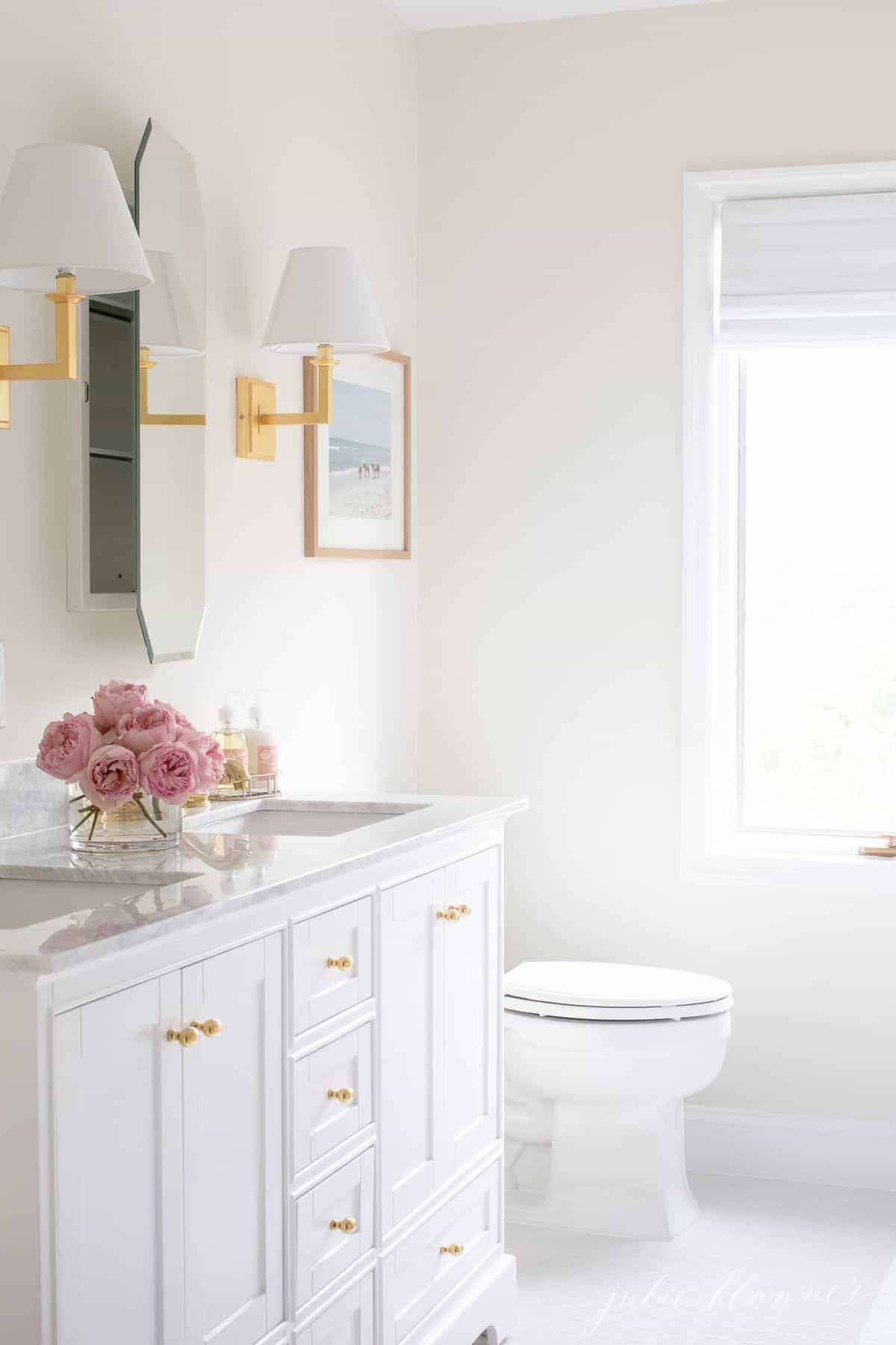 White bathroom with gold touches, mirrored medicine cabinet is slightly ajar. #spabath