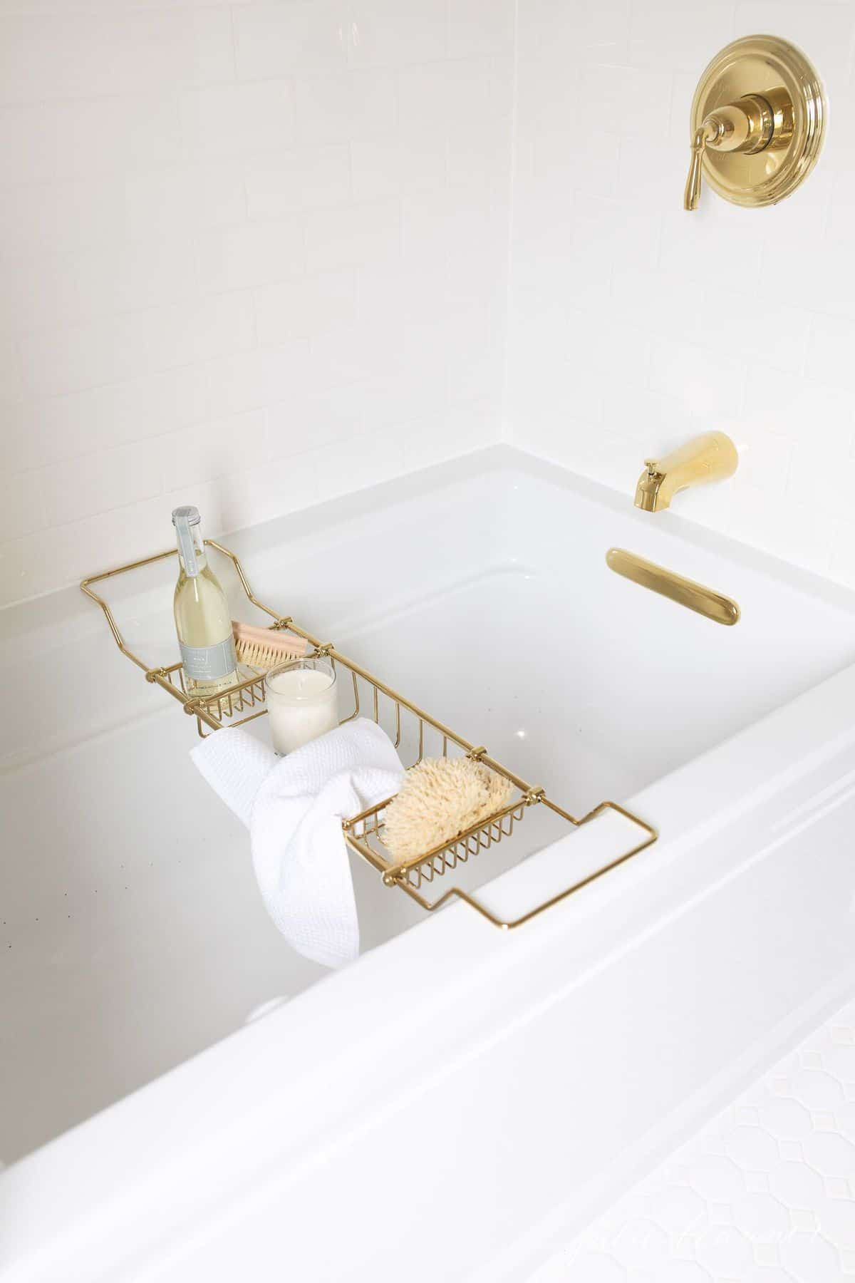 Air tub with brass bath fittings and a brass bath tray filled with relaxing spa treatments. #spabath #spatub