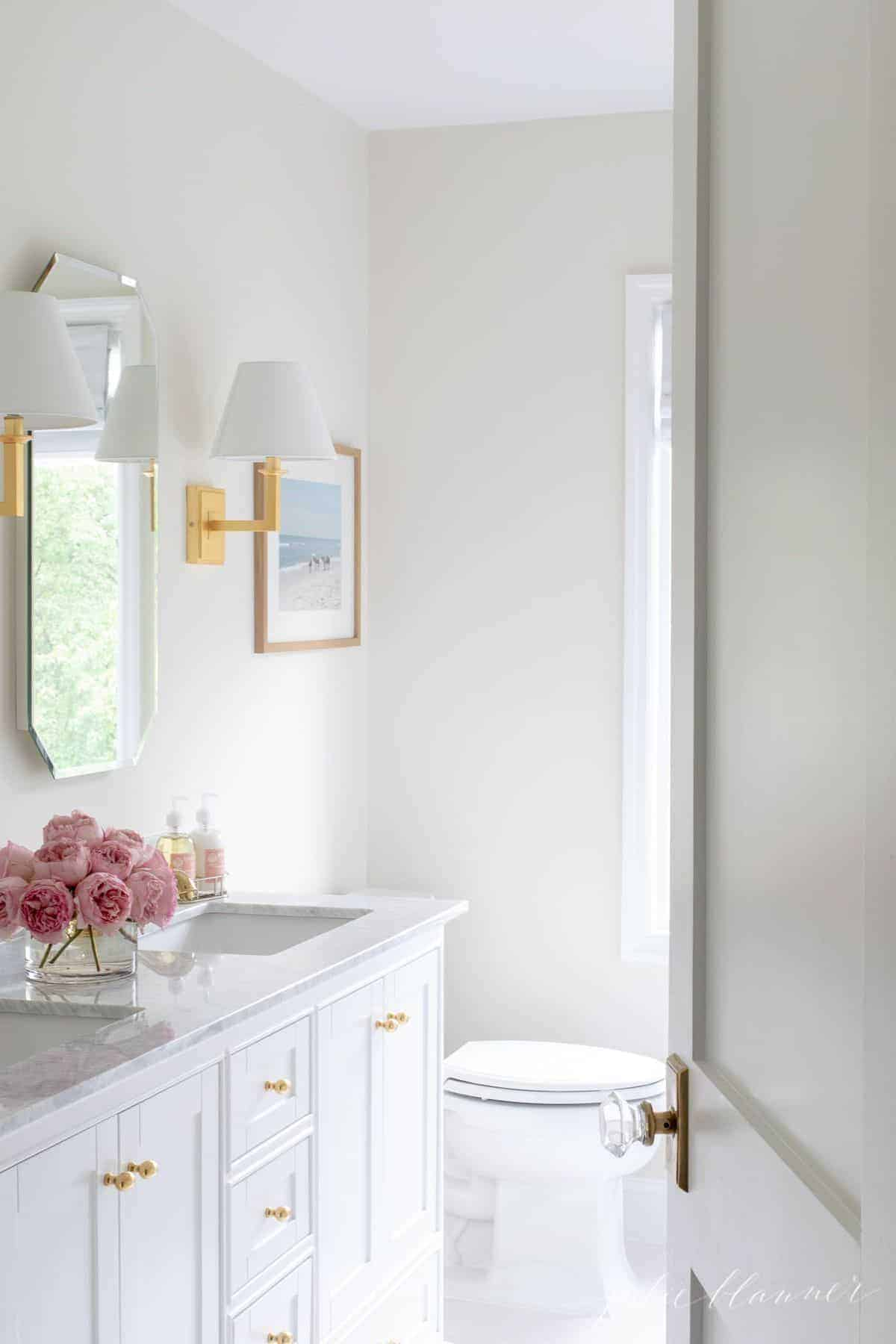 A look into a white bathroom with a door slightly ajar. Gold finishes and pink flowers on the vanity. #spabath