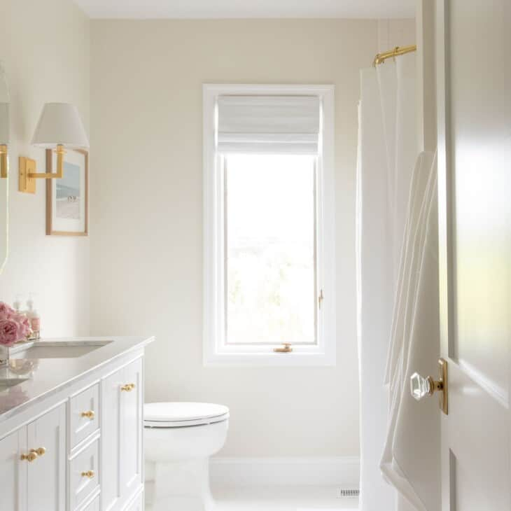 A white bathroom with gold accents.