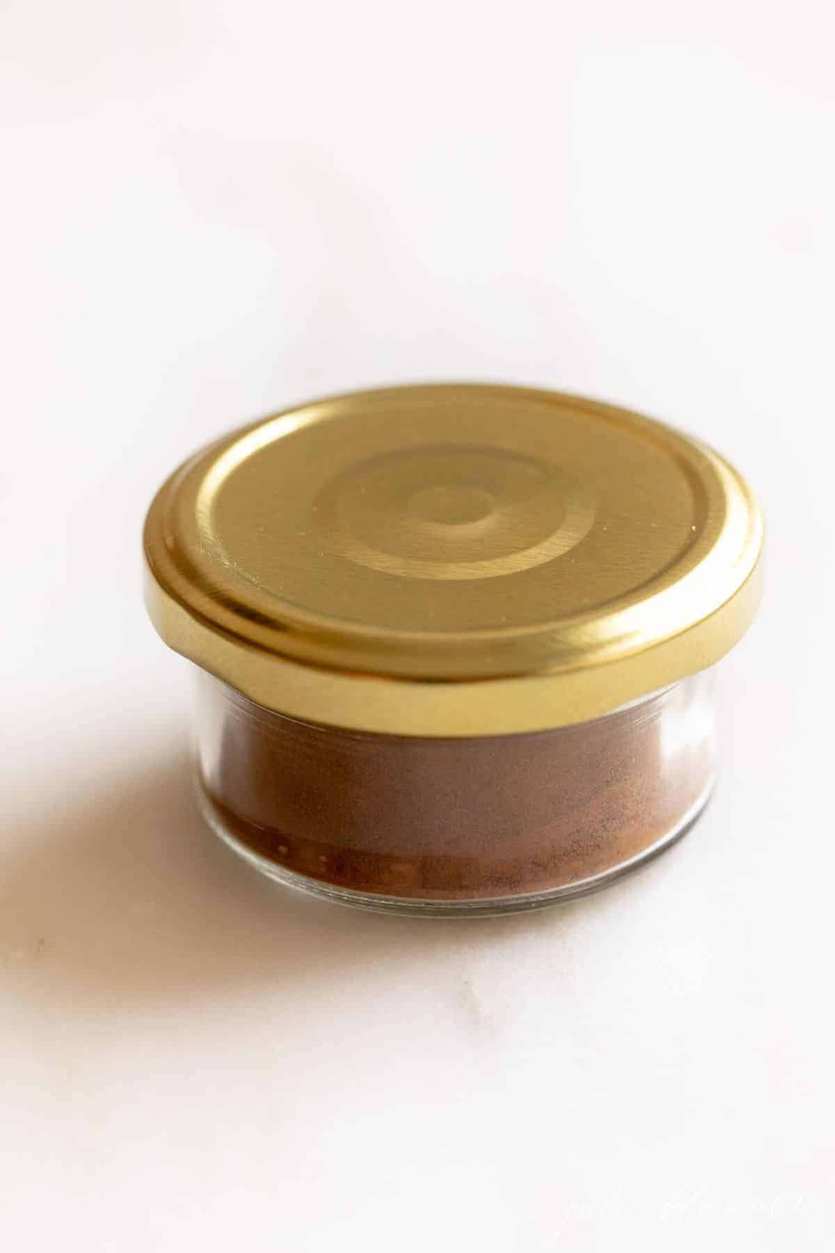 Clear jar of spices with a gold lid, on a white counter top.