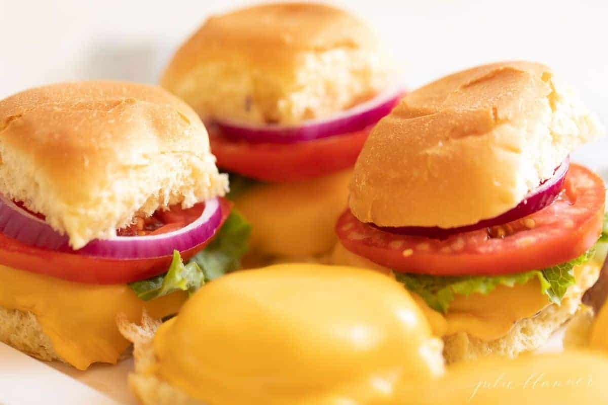 Sliders on a platter, with the front left missing a top bun.