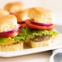 Burgers stacked with lettuce, tomato and onion on a white platter. #burgersintheoven