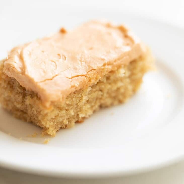 Slice of frosted butterscotch cake on a white plate.