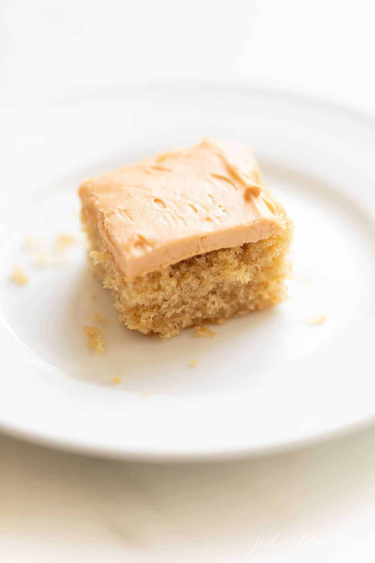 A piece of Butterscotch cake on a white plate, with crumbs surrounding it.
