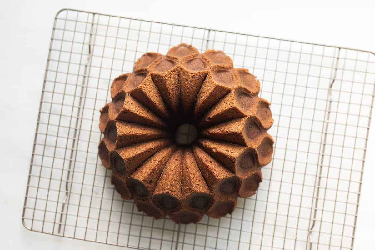 Perfectly formed round bundt cake, placed on a metal baking rack.