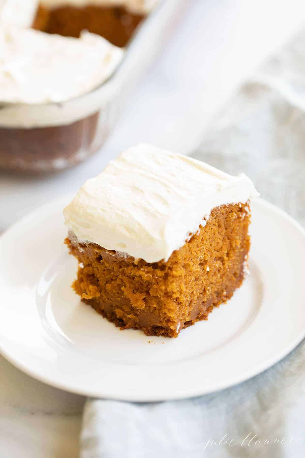 Small white plate with a slice of pumpkin cake, glass baking dish of cake in the background. #pumpkincake #pumpkincakerecipe