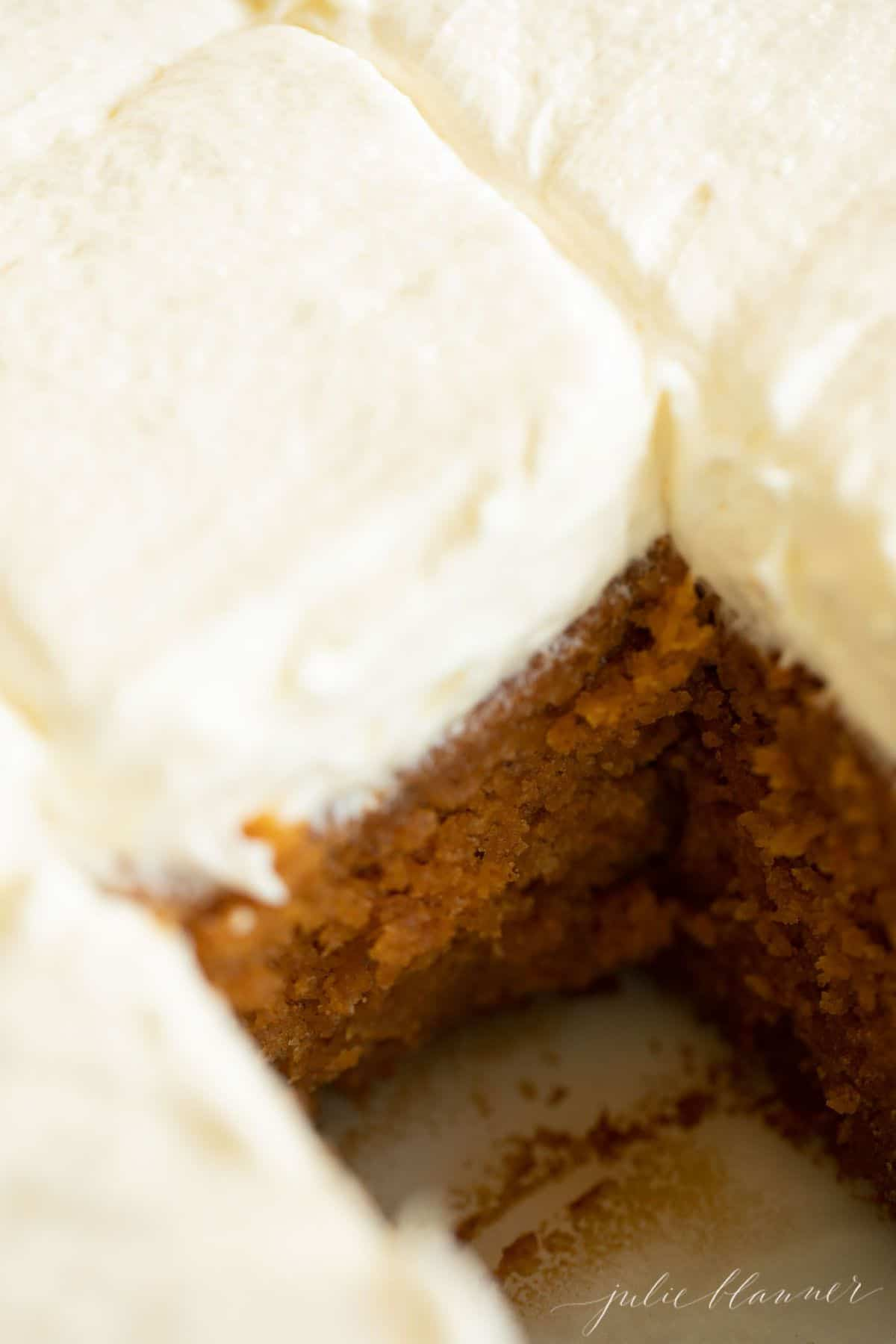 Pumpkin cake frosted with cream cheese frosting on a marble surface, with a piece missing.