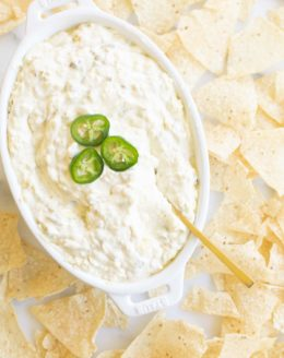 creamy jalapeno dip garnished with fresh jalapenos in a casserole dish surrounded by tortilla chips