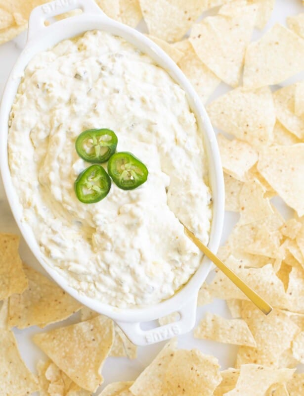 Creamy jalapeño dip in a white dish, chips surrounding it.