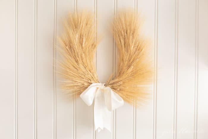 laurel wreath with ivory ribbon hanging on beadboard backsplash