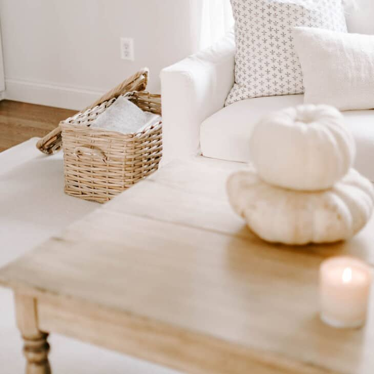 Coffee table featuring a candle and white pumpkins, open basket filled with blankets in background.