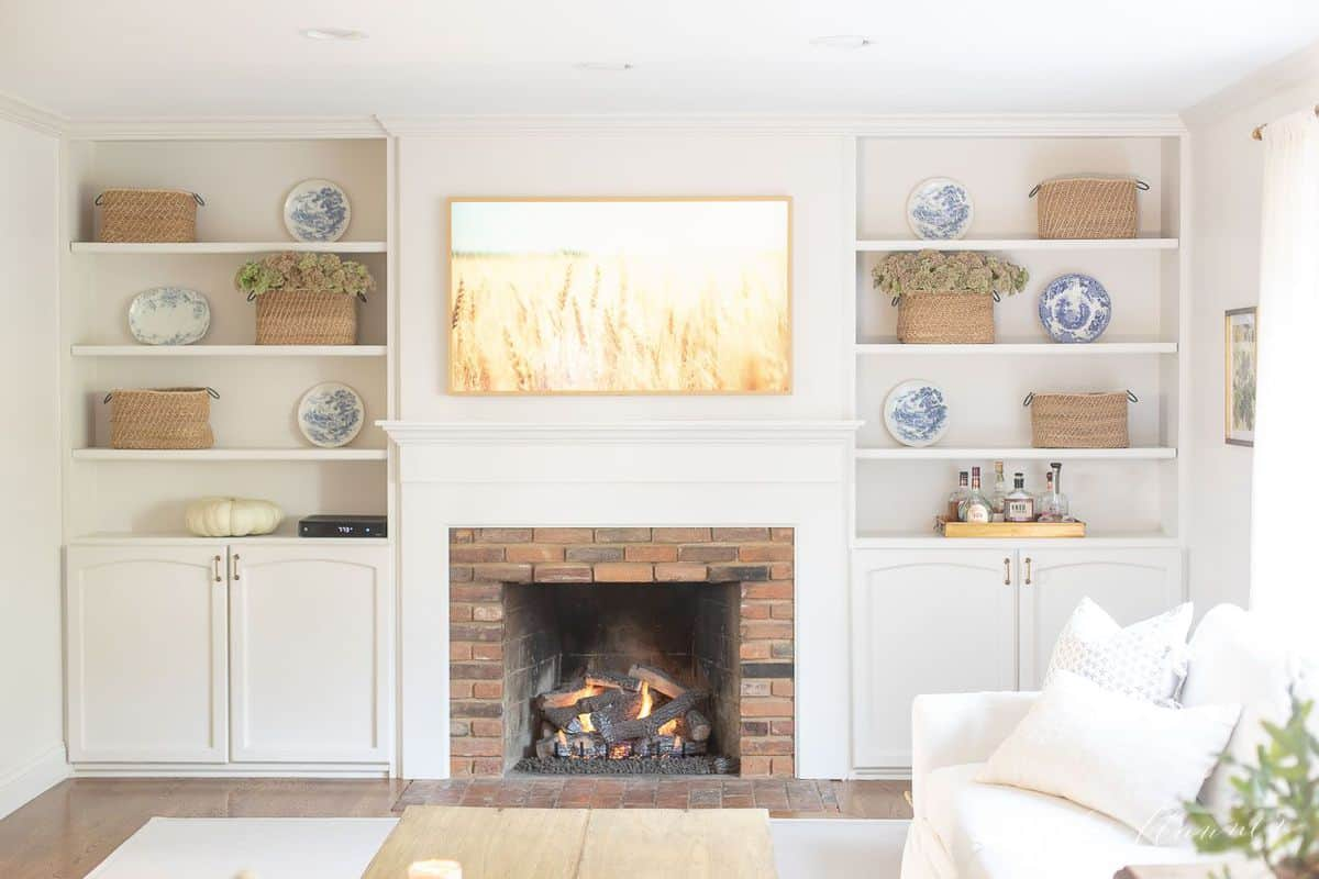 Living room fireplace burning with artwork above and bookshelves on each side. #falllivingroom