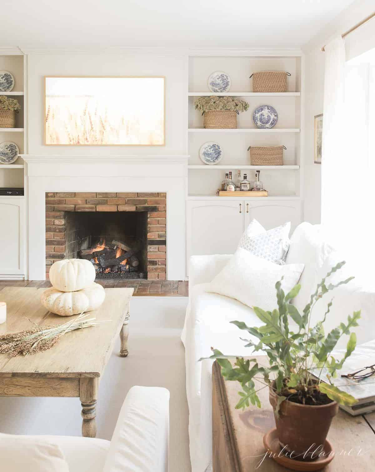 Pulled back view into a living room decorated for fall, pumpkins and wheat on coffee table and fireplace burning in background. #fallharvestdecor