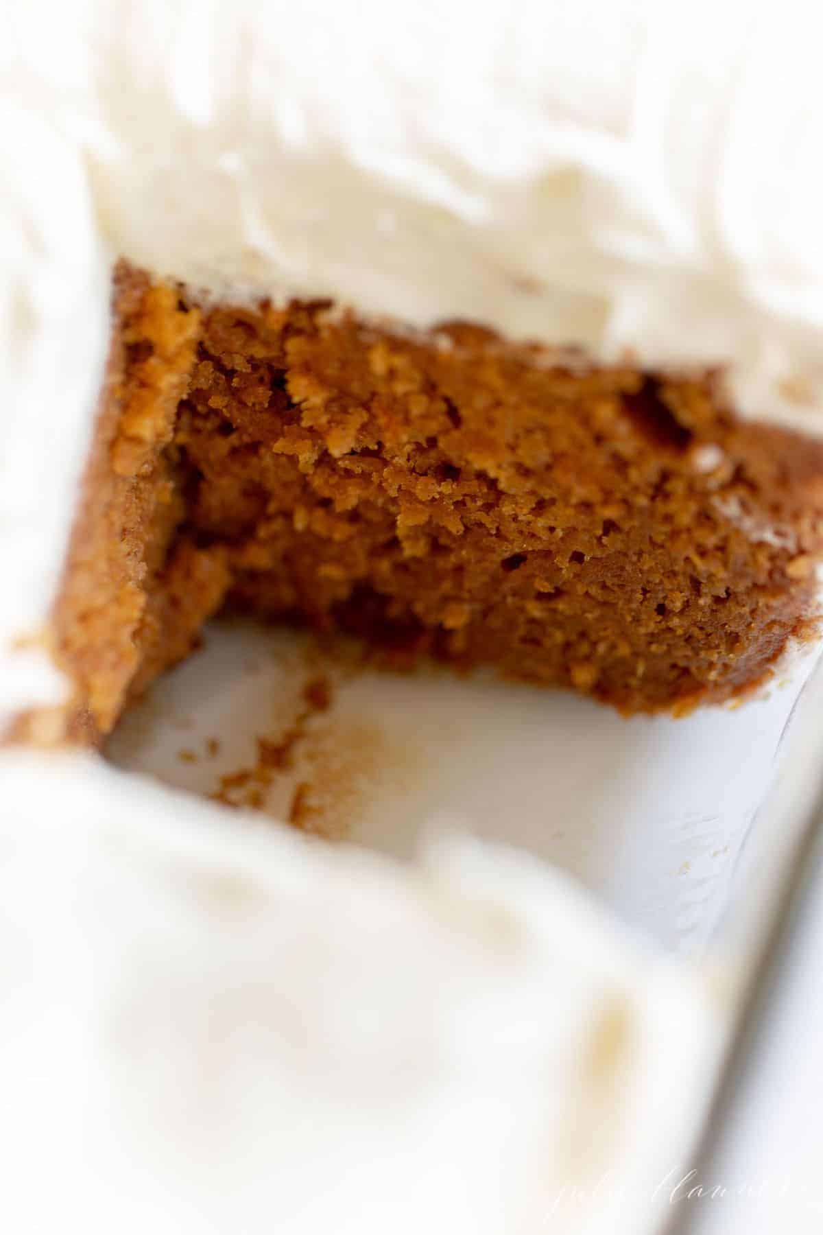 Close up of a pumpkin sheet cake with frosting on top, one slice removed. #pumpkincake