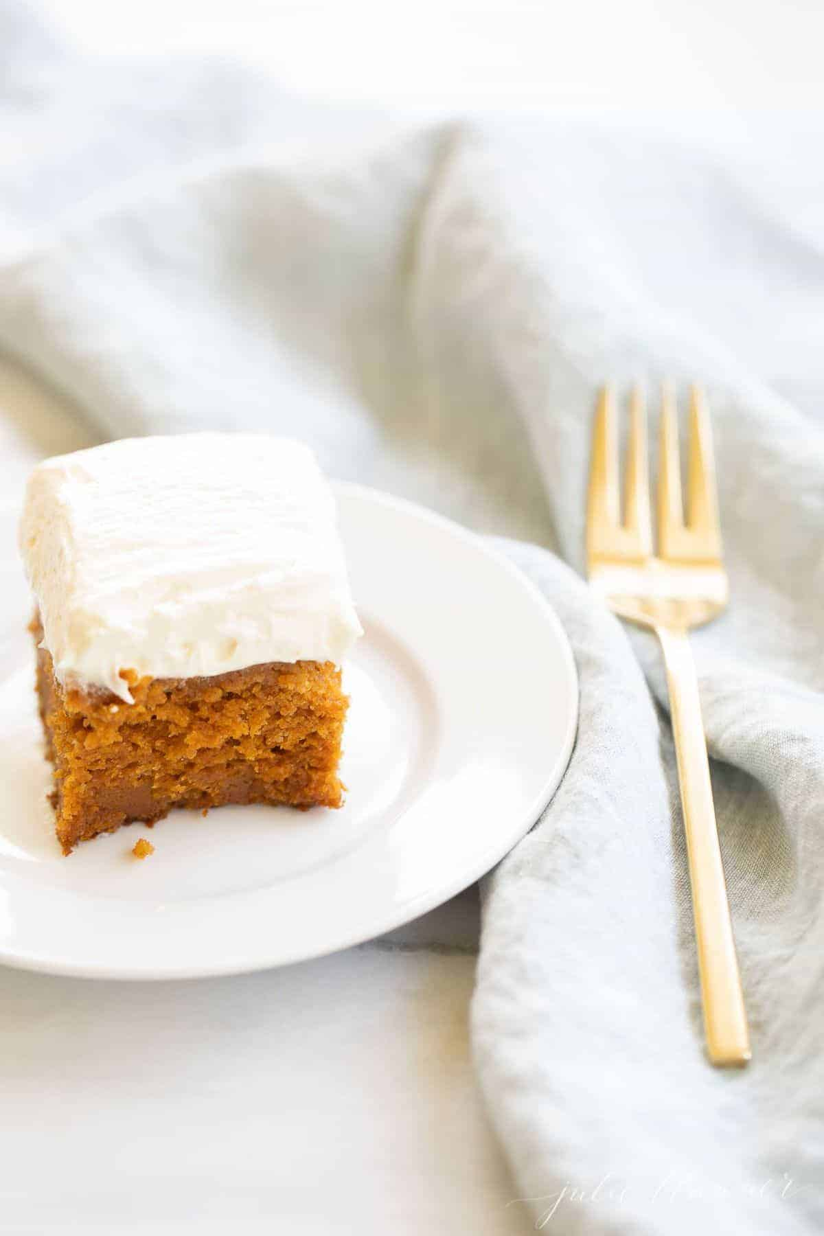 A slice of pumpkin cake on a white plate. Blue linen napkin and gold fork to the side.
