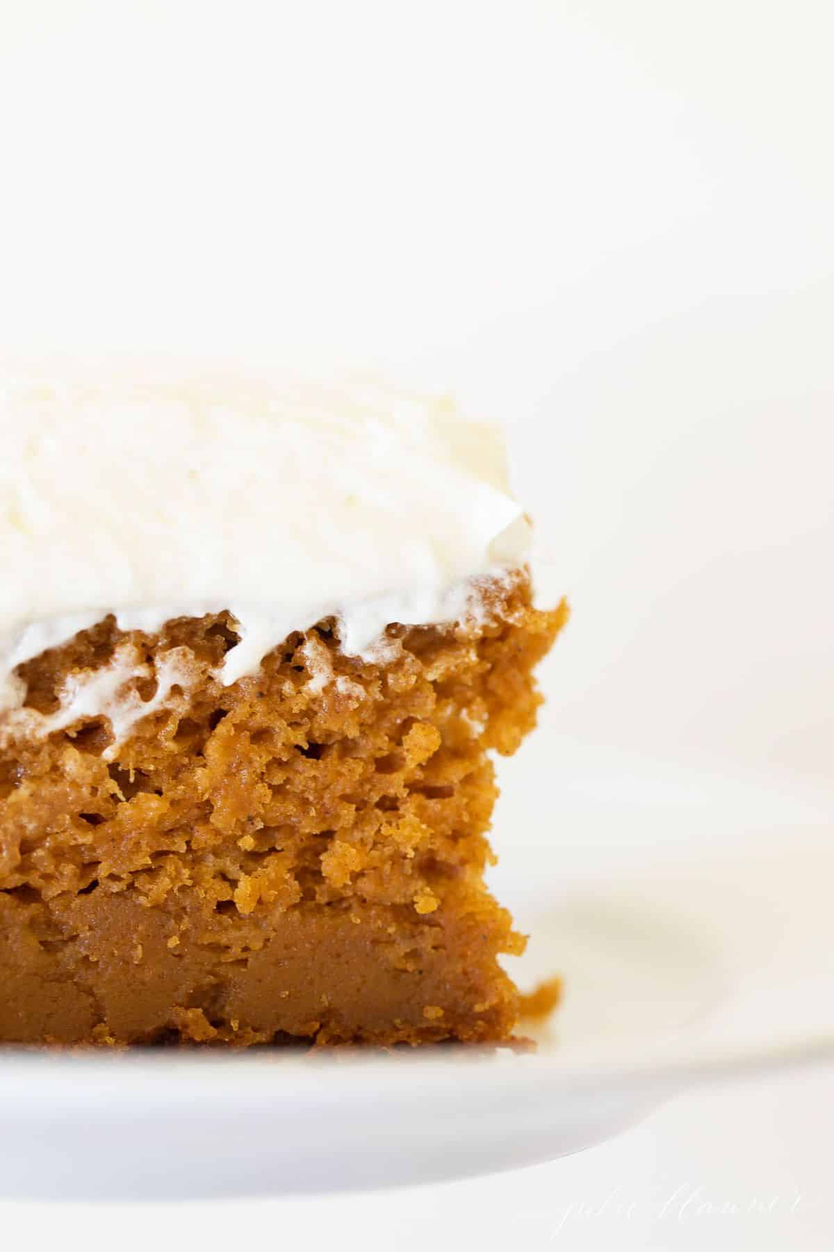 Close-up of a slice of pumpkin cake covered in creamy frosting. #pumpkincake #pumpkincakerecipe