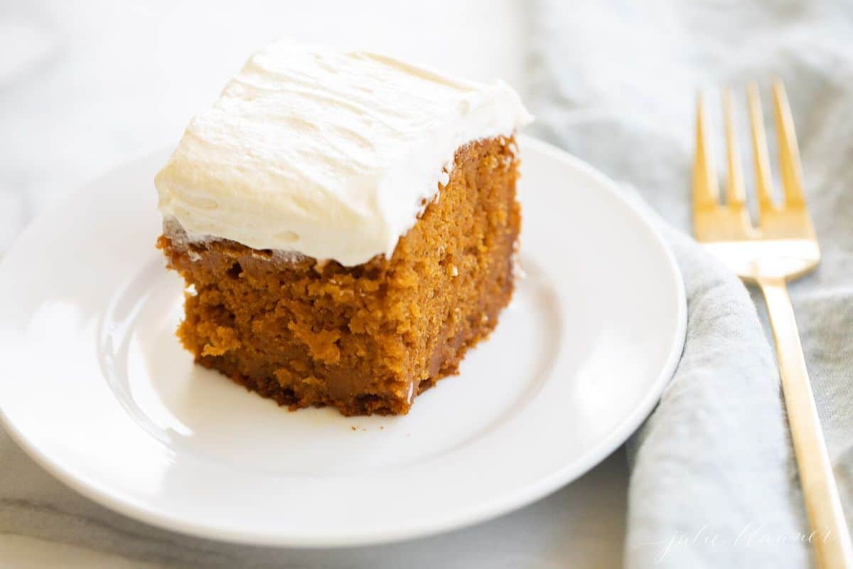 Cut pumpkin bars iced with cream cheese frosting on a white plate on a marble surface.