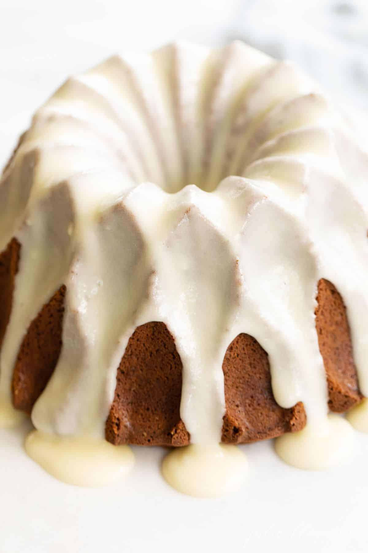 Close up shot of pumpkin bundt cake, covered in cream cheese glaze.