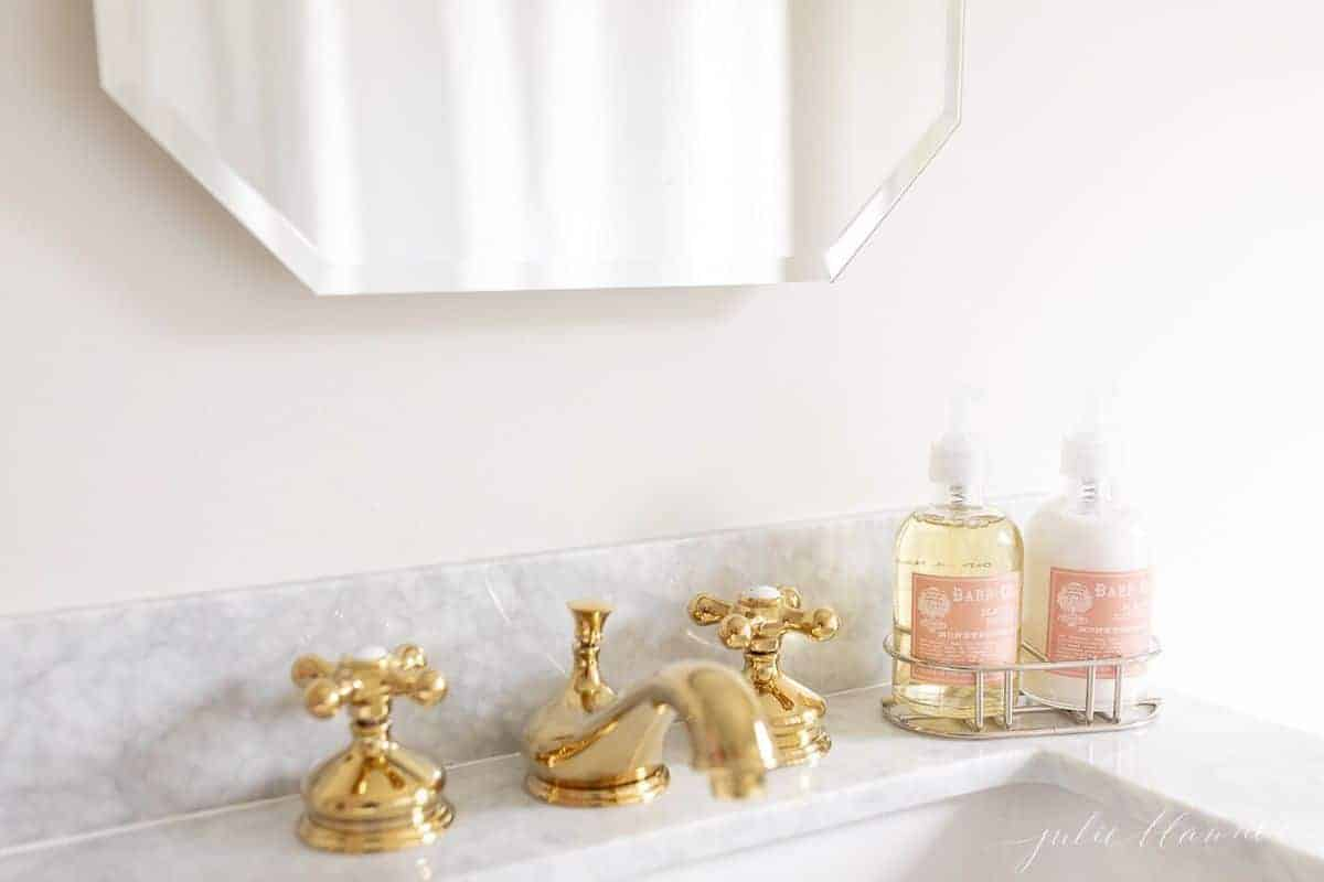 A brass faucet on a marble vanity top, soap and hand lotion to the side. #spatub