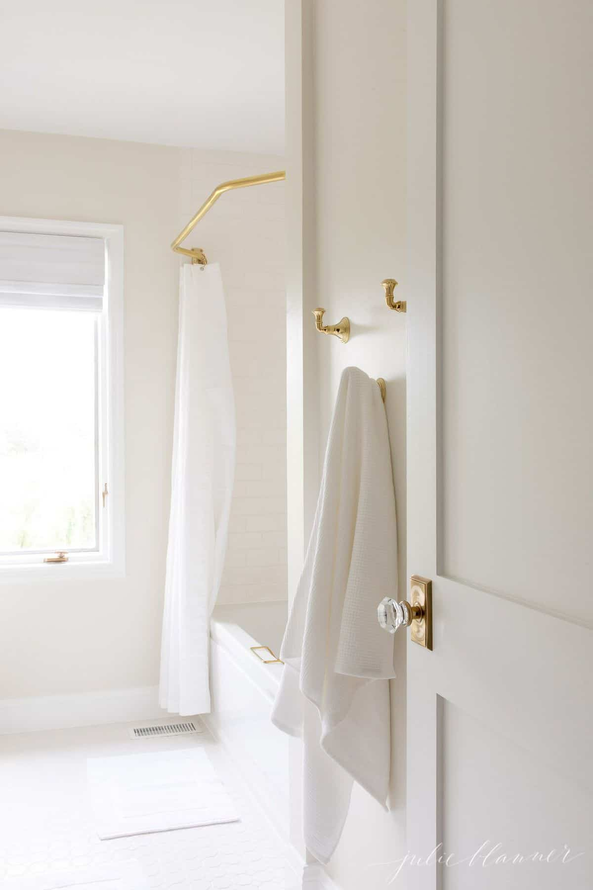 A white bathroom shot featuring brass towel hooks and a brass shower curtain rod.