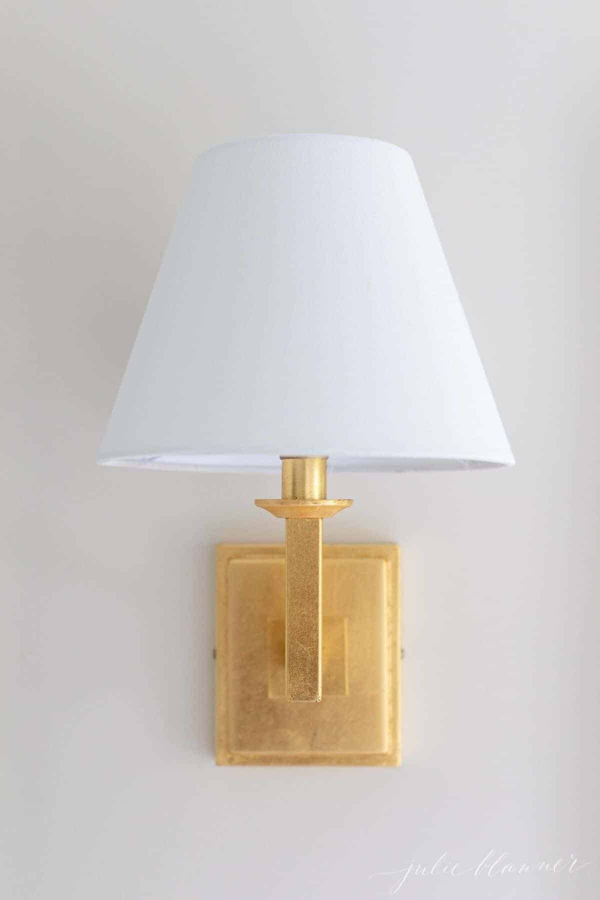 Close-up shot of a classic gold sconce with white shade.