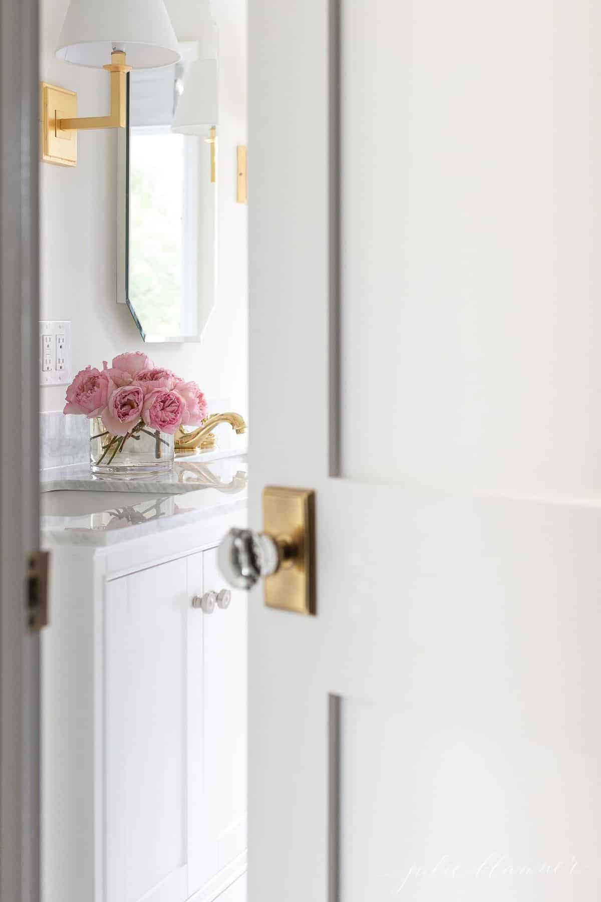 Peaking into a white bathroom past a door that's ajar. #spatub #airtub #showerniche