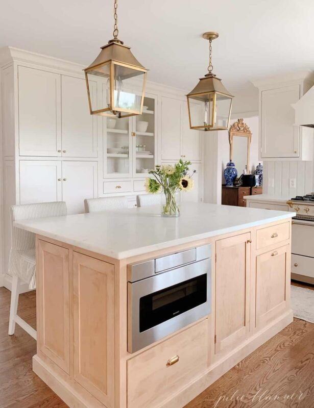 A classic kitchen with cream cabinets, brass hardware and brass lanterns and an under counter microwave drawer.