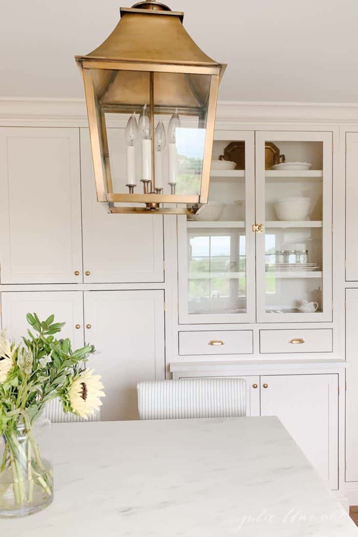 A classic kitchen with cream cabinets, brass hardware and brass lanterns.
