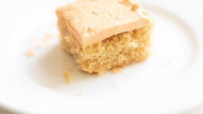 Slice of frosted butterscotch cake on a white plate, crumbs on plate.