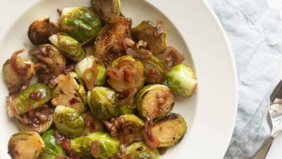 White bowl with sauteed brussel sprouts, blue linen napkin and serving utensil to the side.