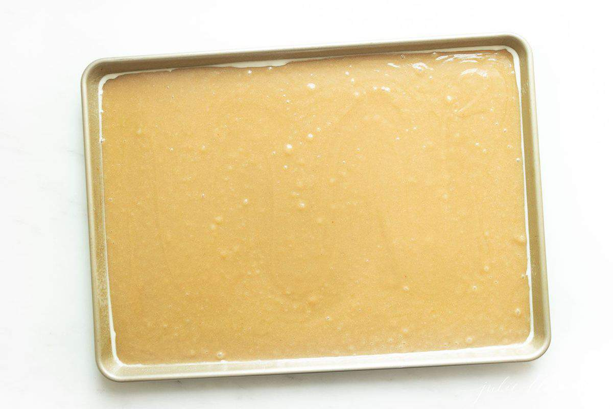 Cake batter poured smooth into a jelly roll pan.