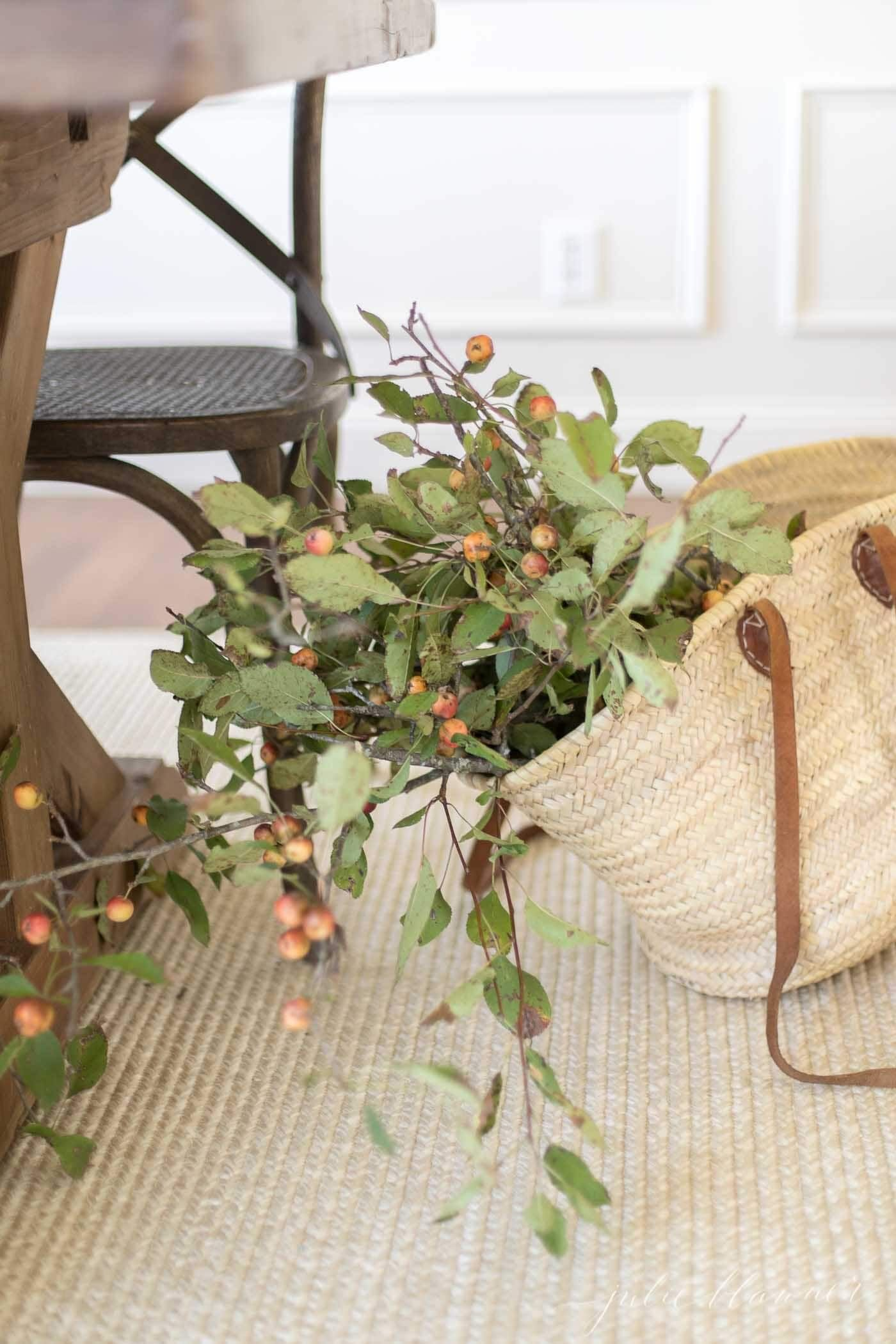 Straw tote full of fall branches with berries.