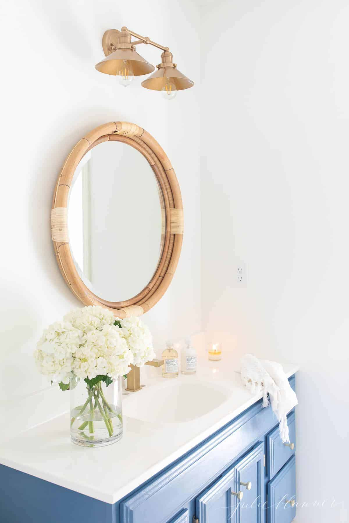 blue vanity in nautical bath with double nautical light fixture