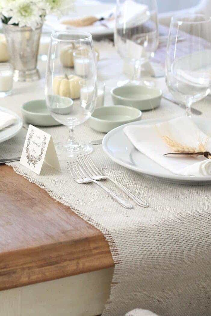 Table set for Thanksgiving, wheat on top of napkins at place setting.