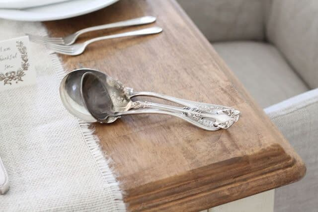 Wooden farm table, antique silver serving utensils on the edge.
